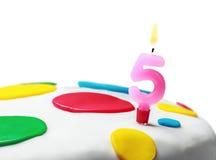 Bougie brûlante avec le numéro cinq sur un gâteau d'anniversaire Photographie stock libre de droits