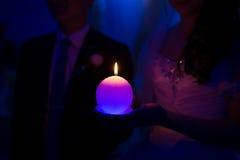 Bougie brûlante dans des mains des nouveaux mariés Photos stock