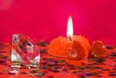 bougie brûlante et coeurs décoratifs sur un fond rouge Photos libres de droits