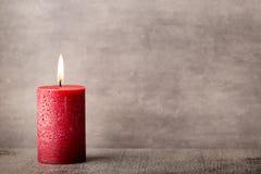 Bougie brûlante rouge sur un fond gris éléments d'intérieur de l'image 3D Photos stock