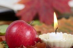 Bougie brûlante avec une pomme rouge Photos libres de droits