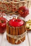 Bougie décorée des bâtons de cannelle et du panier des pommes Photo stock