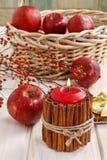 Bougie décorée des bâtons de cannelle et du panier des pommes Image stock