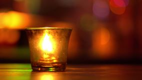 Bougie dans un séjour en verre sur la table en bois dans la barre de musique de bleus Backround brouillé Bokeh Illumination color clips vidéos