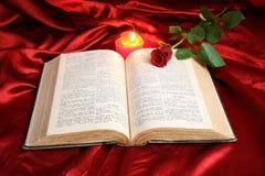 Bougie de coeur sur la bible et la rose ouvertes de rouge Photo stock