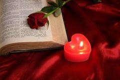 Bougie de coeur sur la bible et la rose ouvertes de rouge Image libre de droits