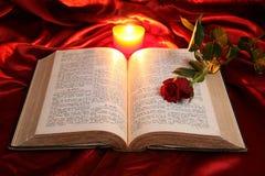 Bougie de coeur sur la bible et la rose ouvertes de rouge Photos libres de droits