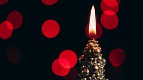 Bougie de Noël brûlant sur un fond de bokeh banque de vidéos