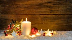 Bougie de Noël ou d'avènement avec les ornements de Noël rouge et blanc et la lumière de fête photo libre de droits