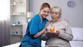 Bougie de soufflement ?treignante volontaire de dame pluse ?g? sur le g?teau d'anniversaire, service hospitalier image stock