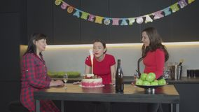 Bougie de soufflement de femme heureuse sur le gâteau d'anniversaire clips vidéos