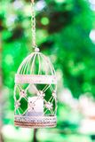Bougie de vintage dans la cage à oiseaux décorative Cage à oiseaux blanche sur le fond floral Décoration de mariage, feuillage ve Photos stock