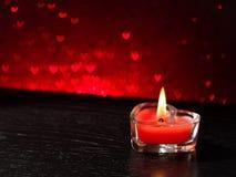 Bougie en forme de coeur brûlante de rouge sur le bokeh rouge de coeurs Image stock
