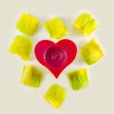 Bougie en forme de coeur entourée par des fleurs Image libre de droits