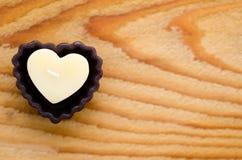 Bougie en forme de coeur sur le fond en bois Photographie stock