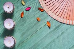 Bougie et fan de zen avec des hiéroglyphes sur un fond en bois Image stock