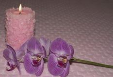 Bougie et orchidée brûlantes sur le fond de textile avec des coeurs Photos libres de droits