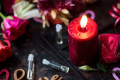 Bougie et parfum flamboyants dans des bouteilles en verre Photo stock