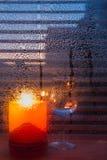 Bougie et verre à vin derrière le verre humide sur la ville Backgr de soirée Image libre de droits