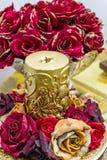 Bougie fleurie d'or avec les roses rouges Photographie stock libre de droits