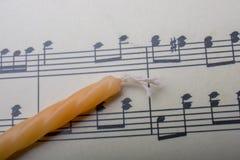 Bougie placée sur le papier avec les notes musicales Image libre de droits