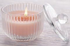 Bougie rose brûlant dans un becher en verre sur une vieille table en bois blanche photo stock