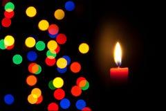 Bougie rouge avec les lumières colorées defocused Photo stock