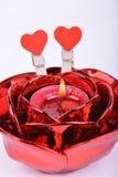 Bougie rouge dans le chandelier et coeurs rouges sur le fond blanc Photographie stock libre de droits
