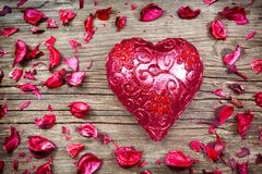 Bougie rouge en forme de coeur avec des pétales de fleur Images libres de droits