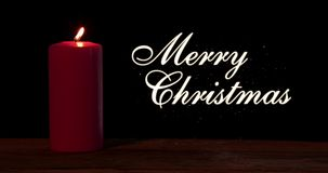 Bougie rougeoyante avec le texte de Joyeux Noël banque de vidéos