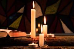Bougie sur une table en bois de vieux chêne Beau fond de vitraux Concept de religion photos stock
