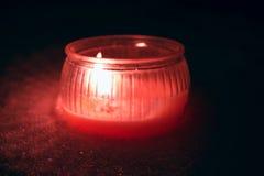 Bougie texturisée rouge avec la flamme dans la neige pendant l'obscurité Photographie stock