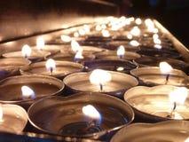 Bougies éclairées dans une église Photos stock