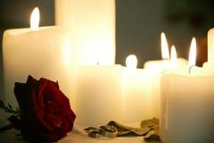 Bougies avec des anneaux et des roses Photographie stock libre de droits