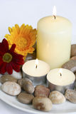 Bougies avec des cailloux et des fleurs Image stock