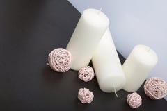 Bougies blanches en couleurs parmi les boules décoratives, tissées des matériaux naturels photographie stock libre de droits