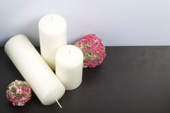Bougies blanches en couleurs parmi les boules décoratives, tissées des matériaux naturels images libres de droits