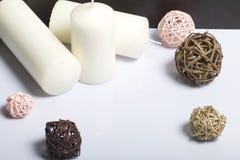 Bougies blanches en couleurs parmi les boules décoratives, tissées des matériaux naturels photo stock