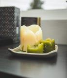 Bougies blanches et vertes sur une étagère Image stock
