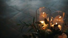 Bougies brûlantes avec le beau bouquet de différentes fleurs sur un plancher de parquet Bougies de brûlure en verres banque de vidéos