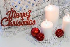 Bougies brûlantes blanches, joyeuse inscription de rouge de Cristmas Photos libres de droits