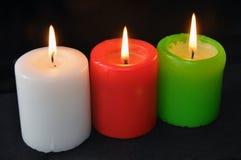 Bougies brûlantes colorées réglées sur le fond noir image libre de droits