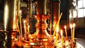 Bougies brûlantes dans le lustre d'or d'église Plan rapproché visuel dans l'église orthodoxe clips vidéos