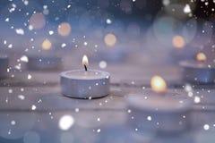 Bougies brûlant sur la planche en bois Images stock