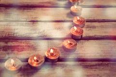 Bougies brûlant sur la planche en bois Photographie stock libre de droits