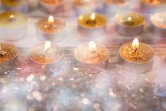 Bougies brûlant sur la planche en bois Image stock