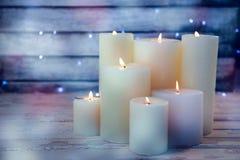 Bougies brûlant sur la planche en bois Photos stock