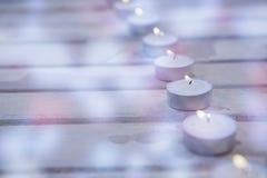 Bougies brûlant sur la planche en bois Photos libres de droits