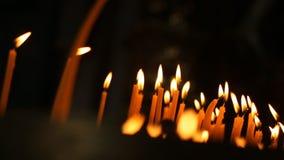 Bougies brûlantes Beaucoup de bougies brûlent sur un chandelier banque de vidéos