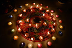 Bougies brûlantes décorées dans le rangoli coloré Photos libres de droits